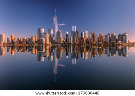 Lower Manhattan skyline panorama over East River with reflection at sunset 2 - stock photo