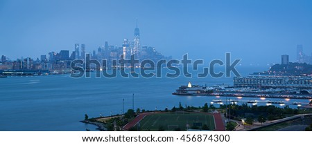 Lower Manhattan with heavy rainfall in evening and Financial District skyscrapers and Weehawken, New Jersey waterfront. New York City - stock photo