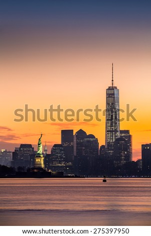 Lower Manhattan with the Statue of Liberty and Freedom Tower at sunrise - stock photo