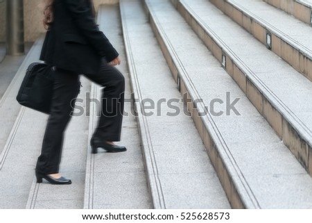 Lower part of business woman in formal suit walking up the outdoor stair with motion blur effect.