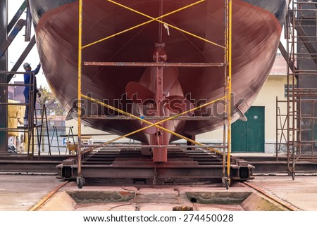 Lower part of stern and propeller detail of a fishing boat in a shipyard for maintenance - stock photo