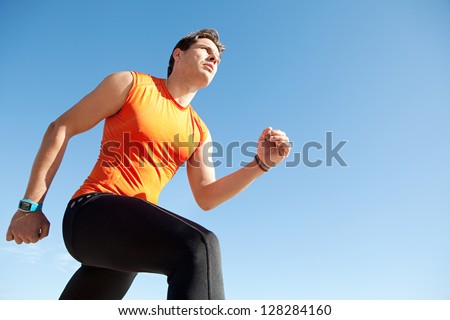 Lower perspective view of a professional olympic sports man running against a bright blue clean sky. - stock photo