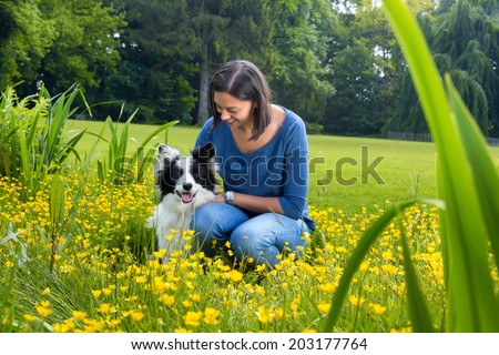 Loyal border collie sitting in buttercups with his boss - stock photo
