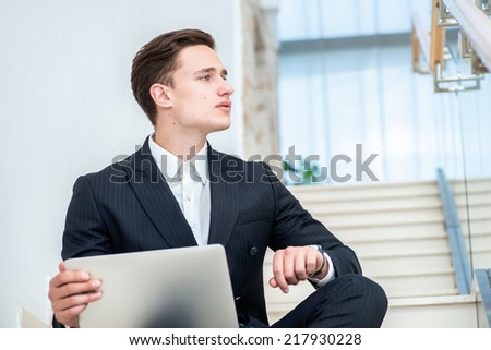 Loyalty to work. Confident businessman sitting on the stairs and works at a laptop and looking forward