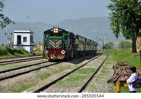 lslamabad, Pakistan - September 20, 2012: Pakistan Railways passenger train to Karachi travels past Golra Sharif on Islamabad's outskirts. Golra Sharif is the site of the Pakistan Railways Museum.  - stock photo