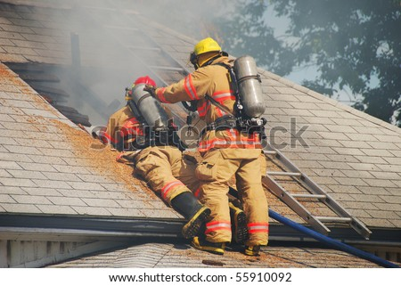 LT Martin and FF Sullivan enlarging the vent hole on a Single family dwelling on fire on SE Mill Street in the Mill Pine Historic District of Roseburg Oregon. - stock photo