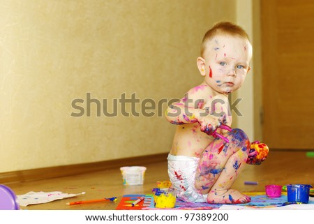 Lttle baby boy playing with a paint - stock photo