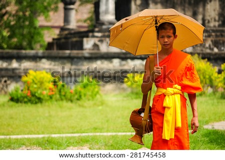 Luang Pra bang, Laos : 13 DEC 2008 Unidentified monks walk to collect alms and offerings.This procession is held every early morning in Luang prabang. - stock photo