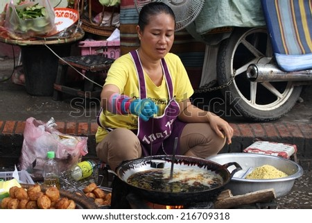 LUANG PRABANG, LAOS - AUGUST 15: A local Laotian Hill tribe woman cooking food at the daily morning market in Luang Prabang, Laos on the 15th August, 2014.