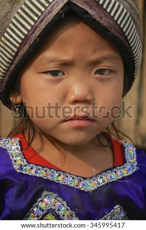 LUANG PRABANG, LAOS - FEBRUARY 11: A young girl in traditional Hmong hill tribe dress with elaborate head, she has  runny nose. 11th February, 2015.