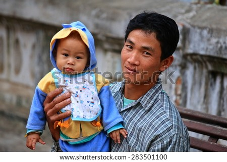 Luang Prabang, Laos - February 13, 2015: Local man showing off his new born baby son proudly to foreign visitors in a small village, Luang Prabang, Laos