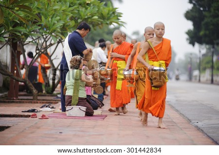 LUANG PRABANG, LAOS- JULY 7, 2011 : Monks gathering morning alms in Luang Prabang.The tradition of giving alms to monks in Luang Prabang has been extended to tourists. - stock photo