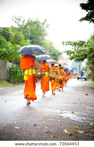 LUANG PRABANG, LAOS - OCTOBER 16 : Buddhist novices walk to collect alms and offerings on Oct 14, 2010 in Luang Prabang, Laos. This procession is held every day. - stock photo