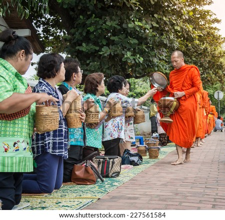 LUANG PRABANG, LAOS - OCTOBER 27; Unidentified monks walk to collect alms and offerings on October 27, 2014 Laos. This procession is held every day in Luang prabang in the early morning.
