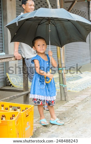LUANG PRABANG, LAOS - SEP 25, 2014: Unidentified Lao little girl in a blue dress with an umbrella. 55% of Laos people belong to the Lao ethnic group