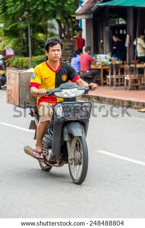 LUANG PRABANG, LAOS - SEP 25, 2014: Unidentified Lao man wearing Manchester United shirt on a motorbike. 55% of Laos people belong to the Lao ethnic group