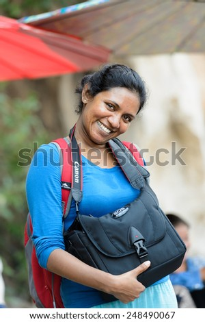 LUANG PRABANG, LAOS - SEP 25, 2014: Unidentified Lao woman with a Canon camera bag. 55% of Laos people belong to the Lao ethnic group