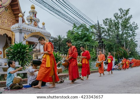 LUANG PRABANG-MARCH 14 :monks collecting food in the street on March 14, 2015 in Luang Prabang, Laos