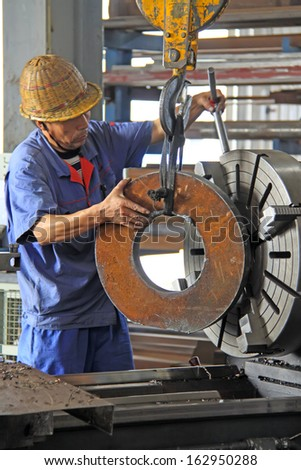 LUANNAN COUNTY - AUGUST 25: Industrial workers on machine in a production line, Xinxin special steel co., LTD, On August 25, 2011, luannan county, hebei province, china.