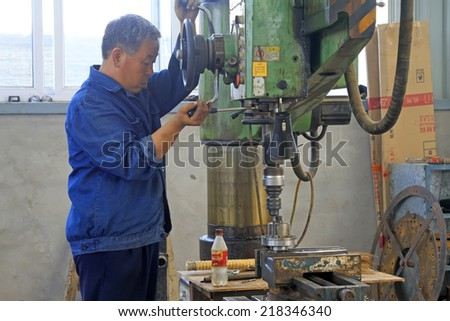 LUANNAN COUNTY - AUGUST 16: Worker in production line in a factory, on august 16, 2014, Luannan County, Hebei Province, China