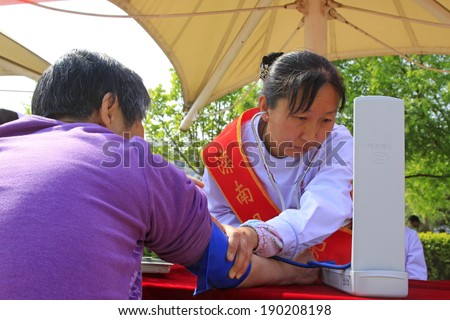 LUANNAN COUNTY, CHINA - APRIL 29: Medical workers for free for the diagnosis of disease on the street, on april 29, 2014, Luannan county, Hebei province, China