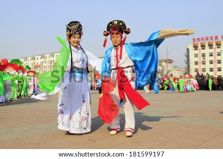 LUANNAN COUNTY - FEBRUARY 11: Buffoon wearing colorful clothes, performing yangko dance in the street, during the Chinese Lunar New Year, February 11, 2014, Luannan County, Hebei Province, China.