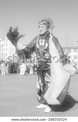 LUANNAN COUNTY - FEBRUARY 9: Old man wearing colorful clothes, performing yangko dance in the street, during the Chinese Lunar New Year, February 9, 2014, Luannan County, Hebei Province, China.  - stock photo