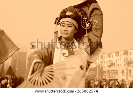 LUANNAN COUNTY - FEBRUARY 12: Young woman wearing colorful clothes, performing yangko dance in the street, during the Chinese Lunar New Year, February 12, 2014, Luannan County, Hebei Province, China. - stock photo