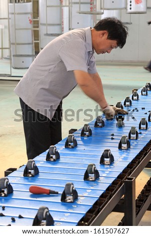 LUANNAN COUNTY - SEPTEMBER 22: A worker on production line in Solar energy factory, on September 22, 2011, luannan county, Hebei province, China.