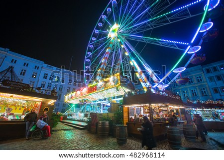 LUBECK, GERMANY - DEC 27: Christmas atmosphere of the city at night. The night holiday illumination. Christmas Fair at night. Ferris, wonder wheel. Lubeck. Germany. Europe. December 27, 2013