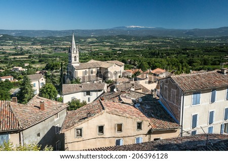 Luberon landscape view with cathedral of Bonnieux and the Mont Ventoux on the background, Provence, France