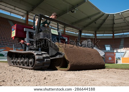 LUBIN, POLAND - JUNE 11, 2015: Worker on the machine laying roll grass on the football playing field at the stadium of Zaglebie Lubin.