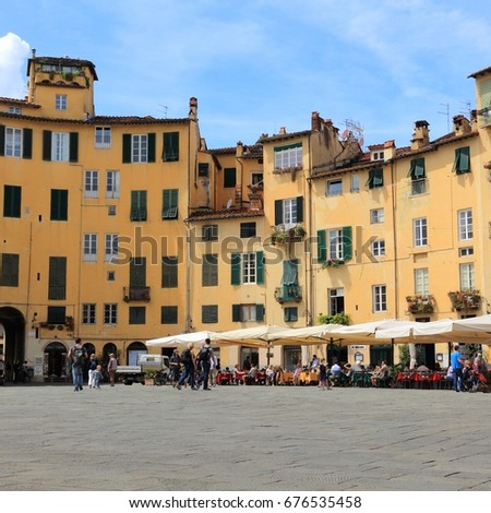 LUCCA, ITALY - APRIL 29, 2015: People visit Old Town square (Piazza Anfiteatro or Amphitheater Square) in Lucca, Italy. Italy is visited by 47.7 million tourists a year (2013).