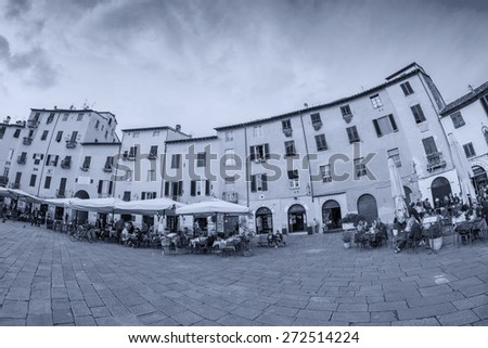 LUCCA, ITALY - APRIL 18, 2015: Tourists and locals in Piazza Anfiteatro. Lucca is one of the most visited town of Tuscany. - stock photo
