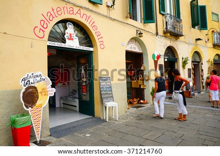 LUCCA, ITALY - AUGUST 19, 2014: People standing in front of a Gelateria Anfiteatro ice salon