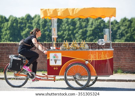 Lucca, Italy-June 7, 2015. Ice Cream Vendor riding her tricycle cart on top of the wall surrounding the ancient city of Lucca, Italy - stock photo