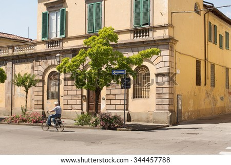 Lucca, Italy-June 6, 2015. People on the streets of a residential section of the ancient Walled City of Lucca, Tuscany, Italy - stock photo