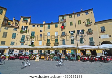 LUCCA, ITALY - SEPTEMBER 21: Bicycles parked in the often filmed Piazza Amfiteatro: September 21, 2015 in Lucca, Italy - stock photo