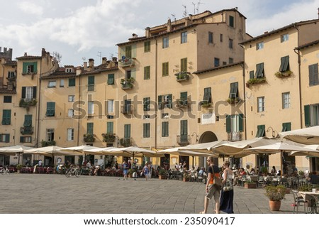 LUCCA, ITALY - SEPTEMBER 06, 2014: Unrecognizable people walk and have a rest in cafes along Amphitheatre square. The Amphitheatre square situated on the old structure of closed Roman amphitheatre.