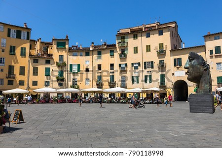 LUCCA, ITALY 07 31 2017- The famous place Piazza Dell´??Anfiteatro with a sculpture of the artist igor mitoraj. beautiful piazza and sightseeing must with restaurants to have a rest.