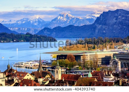 Lucerne old town and Culture center building on Lake Lucerne with snow covered Alps mountains in background - stock photo