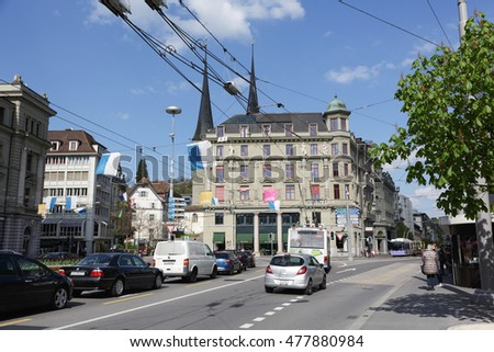 LUCERNE, SWITZERLAND - MAY 04, 2016: Cityscape includes a massive residential building with decorative facade. On the street a few cars in traffic and few people can be seen in the distance