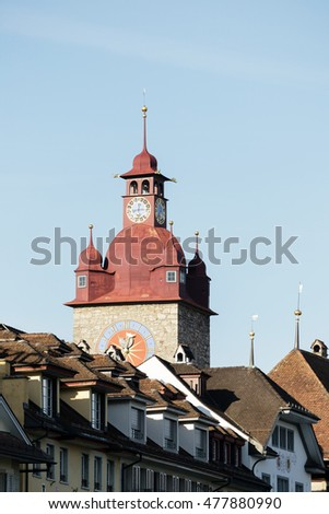 LUCERNE, SWITZERLAND - MAY 04, 2016: Clock tower that is a part of Town Hall towering over other city buildings. The Clock Tower with its huge clock is height over 40 meters.