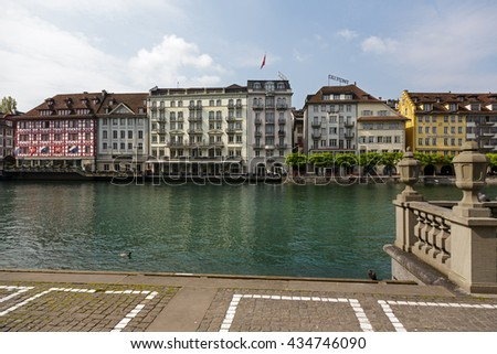 LUCERNE, SWITZERLAND - MAY 02, 2016: Colorful buildings of the city along river Reuss shows its unique character and variety of sightseeing attractions. The town is a destination for many travelers