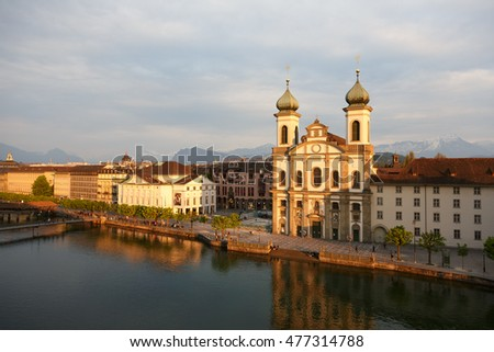 LUCERNE, SWITZERLAND - MAY 02, 2016: Evening view towards buildings on the left bank of river Reuss. Jesuit Church is one of the most visited tourist attractions in the city