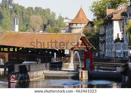 LUCERNE, SWITZERLAND - MAY 05, 2016: General view towards Spreuer Bridge and Nolliturn Tower of Musseg Wall  by the Reuss river in old town. These are sightseeing attractions in the city