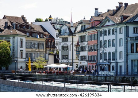 LUCERNE, SWITZERLAND - MAY 08, 2016: Historic buildings located along the river Reuss and many restaurants invites tourists to spend their free time surrounded by variety of sightseeing attractions - stock photo