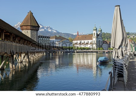 LUCERNE, SWITZERLAND - MAY 05, 2016: Landmarks by the river Reuss. From left can be seen roofed Chapel Bridge with octagonal stone tower and white theater building ending on Jesuit Church.