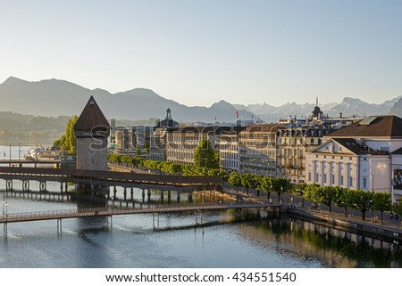 LUCERNE, SWITZERLAND - MAY 06, 2016: Morning view towards the Chapel Bridge together with the octagonal tall tower it is one of the Lucerne's most famous tourists attraction   - stock photo