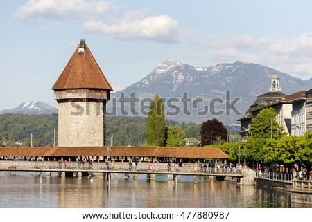 LUCERNE, SWITZERLAND - MAY 04, 2016: Octagonal tower that was built in the river Reuss and is located next to the roofed Chapel Bridge both are the most famous city landmark